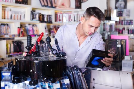 若いハンサムな男の店で大人のおもちゃを購入し、笑顔 写真素材