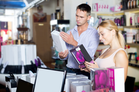 Happy male consultant advising customer shopping sex toy in store for adults. Focus on the woman