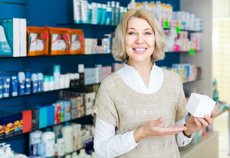 Portrait of mature woman chooses drugs at the pharmacy
