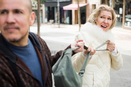 accosting: Portrait of frightened woman and robber stealing bag Stock Photo