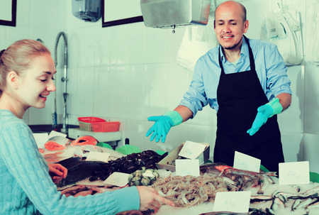 fishery products: Young smiling blonde woman selecting cooled fish at fishery Stock Photo