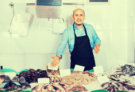 happines: Positive mature salesman with apron offering fresh fish in shop Stock Photo