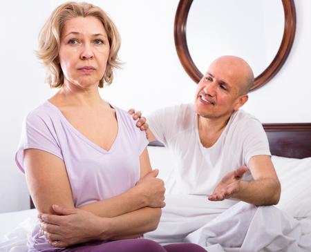 Mature  girlfriend consoling grieving man sitting apart