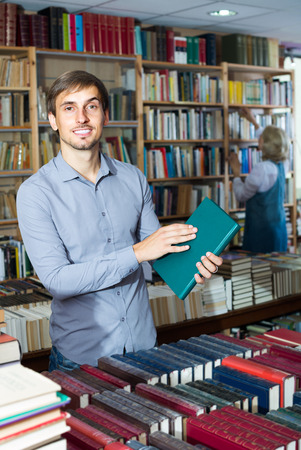 seller: ?Young smiling  man holding book in hard cover in book store Stock Photo