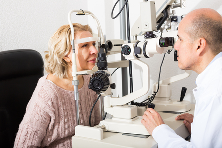 Elderly male ophthalmologist and female pensioner checking eyesight in clinic