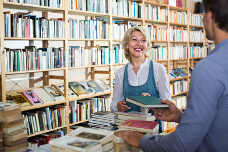 the sixties: portrait of glad mature woman talking to assistant in book store