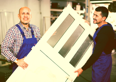 workers with finished PVC profiles and windows at factory Stock Photo