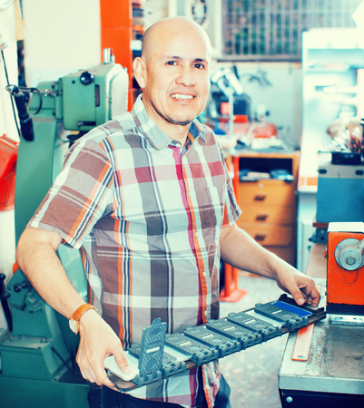 diligente: hombre mayor positivo diligente haciendo el número de vehículos en la máquina en el taller