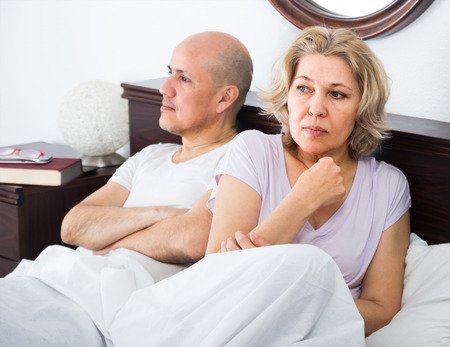 impotent: Mature angry man and his stressed wife sorting out relationships in bed. Focus on woman