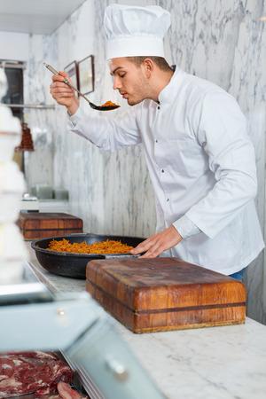 diligente: Joven diligente amable cocinero profesional olfateando plato recién cocinado en la tienda
