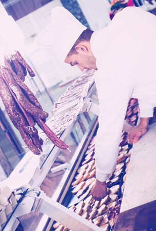 uncooked bacon: Glad young cook in white uniform in grocery shop offering meat and cheese