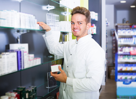 Happy pharmacist wearing uniform and working in pharmaceutical shop
