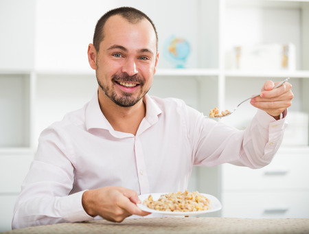 Young happy european businessman in office eating porridge for breakfast Stock Photo