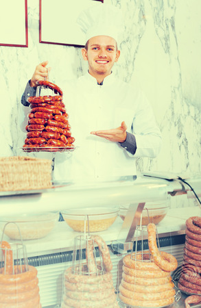 uncooked bacon: Smiling ordinary man seller working at meat market Stock Photo