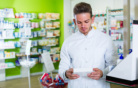 buying questions: Positive man wearing white coat standing among shelves in drug store Stock Photo