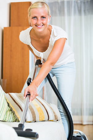 Cheerful young blonde woman in jeans vacuuming floor and furniture