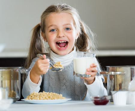 Little girl eating tasty porridge at kitchen table indoors