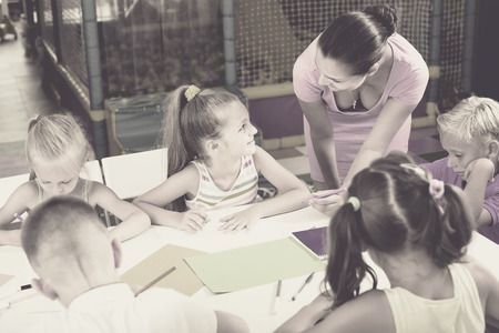 niÑos contentos: Glad children drawing on lesson in elementary classroom  with help of teacher Foto de archivo