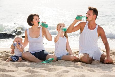 Couple espagnol joyeux avec deux enfants buvant de l'eau douce sur une plage de sable