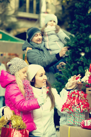 Happy family buying christmas decorations at market. Focus on woman and girl
