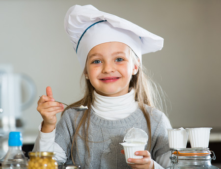 Portrait of female child with white tasty cream indoors