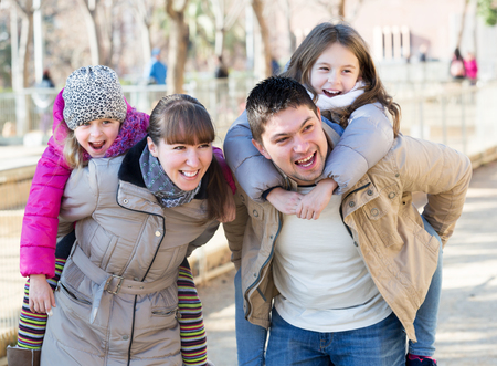 Portrait of happy young parents playing with little daughters at slide of playground. Focus on parents