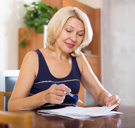 smiling mature woman filling in paper at home interior Stock Photo