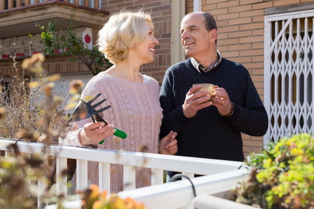horticultural: Smiling elderly woman with horticultural sundry and aged man drinking tea in patio Stock Photo