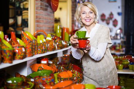 utensilios de cocina: Retrato del cliente sonriente de la mujer madura que sostiene la taza de cerámica