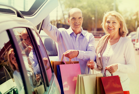 novelties: Smiling mature couple with purchases staying near opened boot