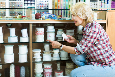 Smilling woman choosing ribbon or elastic band for her sewing hobby at store