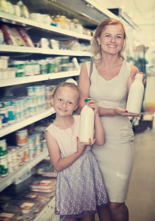 Portrait of smiling woman and girl holding bottle with fresh milk in grocery shop Stock Photo