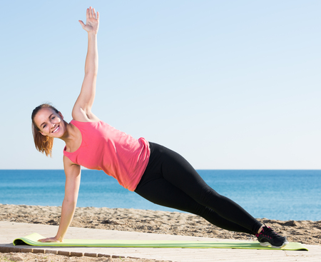 Charming girl exercising on exercise mat outdoor at the seaside