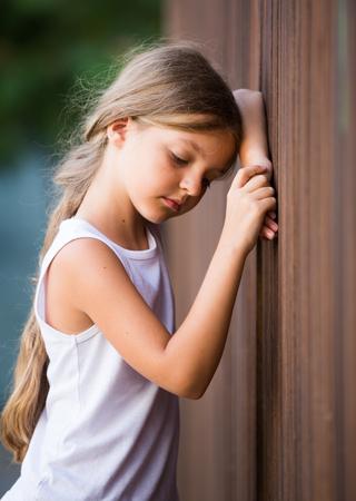 girl in elementary school age looking depressed outdoors in park