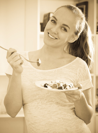 17 20: portrait of happy young woman with chestnut hair eating salad at kitchen Stock Photo