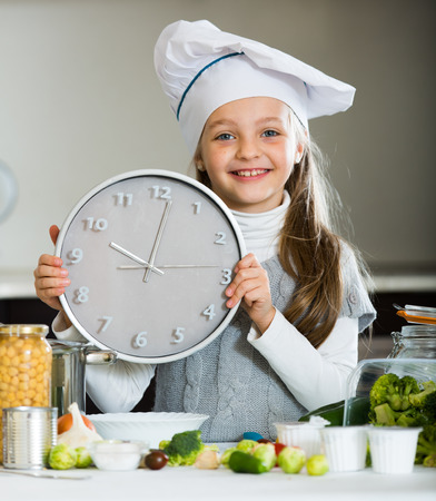 Portrait of cute little girl counting time down when cooking Stock Photo