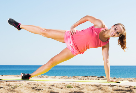 perspire: Young happy woman doing yoga at beach on a sunny day