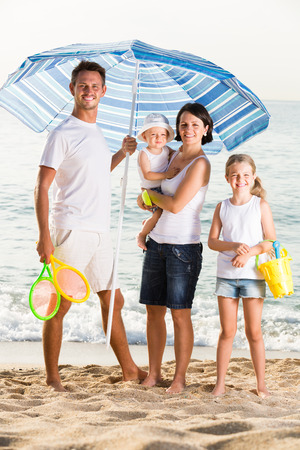 plastic scoop: Happy european man and woman with two kids standing together under beach umbrella on beach