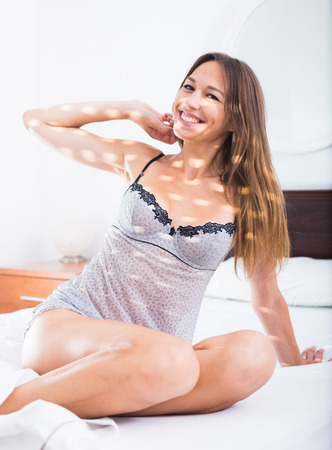 nightwear: young relaxed woman in nightwear sitting in morning sunbeams in bedroom and stretching herself