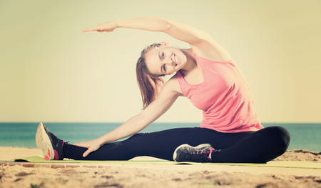 perspire: young happy woman exercising on exercise mat outdoor at the seaside
