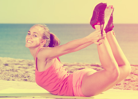 perspire: Happy woman in sportswear training  at sea beach on sunny day