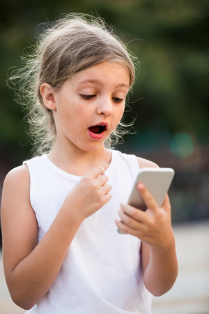 gasping: girl in elementary school age is very surprised while looking at mobile phone outdoors on summer day Stock Photo