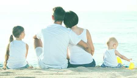 personas abrazadas: back view on couple with two little kids  sitting on the sandy beach and looking at sea