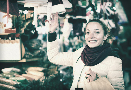 lifestile: Portrait of positive female customer near counter with Christmas gifts in evening time