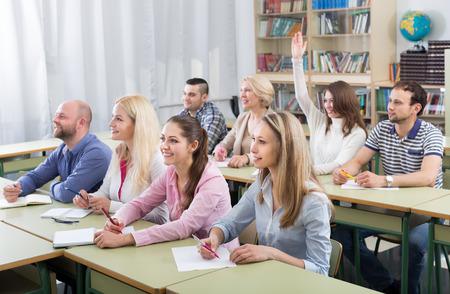 cuadro sinoptico: estudiantes adultos atentos diligentemente anotando el resumen en el aula