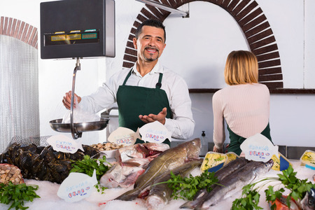 fish selling: Positive cheerful  shop assistants selling fresh fish and chilled seafood