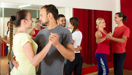 latino dance: Positive adult people dancing Latino dance in class