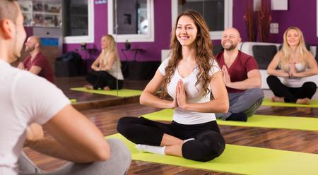 estudiantes adultos: El entrenador que muestra a estudiantes adultos nueva postura de yoga en clase