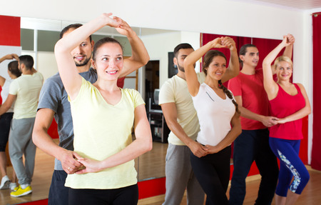 latino dance: Smiling young couples dancing Latino dance in class Stock Photo