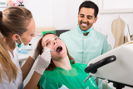 Sad young patient checking out her teeth at dentist Stock Photo